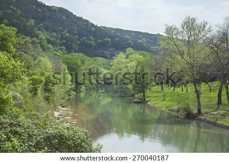 The Guadalupe River below cliffs of the Texas Hill Country during Spring - stock photo