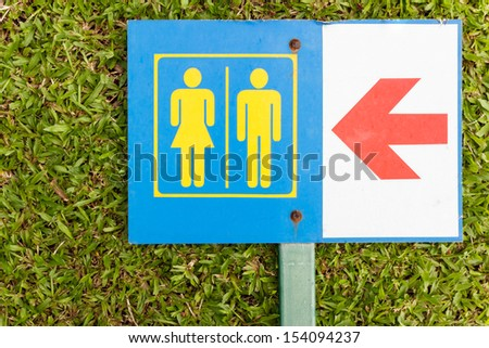 The Guide post arrow to restroom for men and women on grass - stock photo