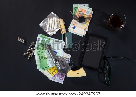 The gun, euro banknotes, drugs, tablet pc on black background - stock photo