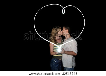 The guy and the girl draw heart and kissing. Isolate on black - stock photo