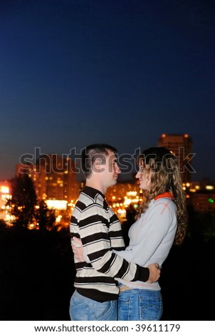 The guy and the girl embrace against a night city - stock photo