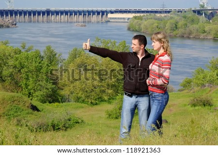 The guy embraces the girl, looks in a distance and shows a thumb. Zaporozhye. Ukraine - stock photo