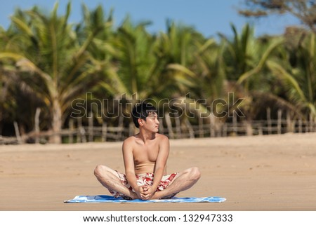The guy of Asian appearance practices yoga on a beach against palm trees - stock photo