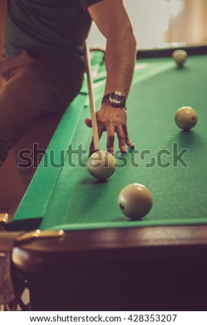The guy plays billiards and aim the ball in the hole. Focus on center of photo. The guy sitting on the edge of the table. - stock photo