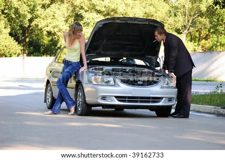 The guy repairs the car, the girl looks at him and smiles - stock photo