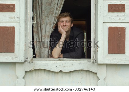 The guy smiles looking out of the window - stock photo