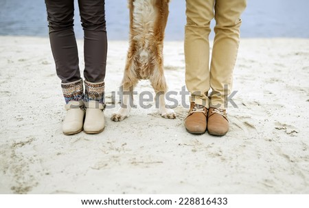the guy, the girl and dog - feet and paws - stock photo
