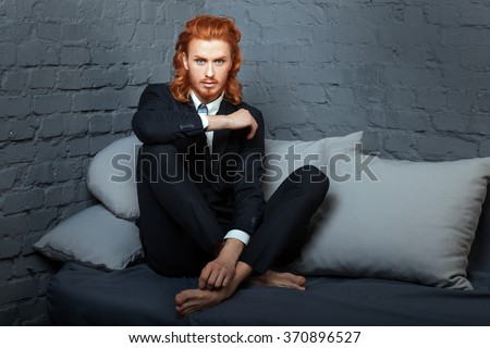 The guy with the red hair and beard, sitting on the sofa. Freckles on his face. - stock photo