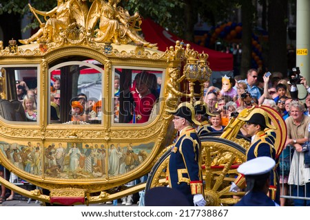 THE HAGUE, HOLLAND - SEPT 16: Queen Maxima waving in golden carriage waving to crowds on the bicentennial Prinsjesdag (opening parliamentary year by King) on September 16, 2014 in The Hague, Holland. - stock photo
