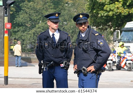 THE HAGUE, HOLLAND - SEPT 21: Young police officers watching the crowd at the Parliament on Prinsjesdag (opening of parliamentary year by Queen) on September 21, 2010 in The Hague, Holland. - stock photo