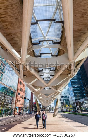 The Hague, Netherlands - April 21, 2016: Netkous viaduct at Beatrixkwartier with RandstadRail station and unidentified people. It is a modern construction designed by Zwarts & Jansma architects - stock photo