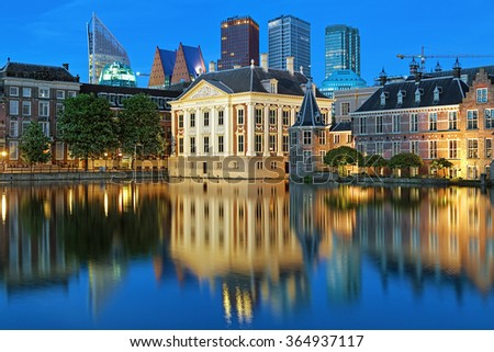 The Hague, Netherlands. The Mauritshuis on the shore of Hofvijver Pond (Court Pond) on the background of the city's skyscrapers in the evening. - stock photo