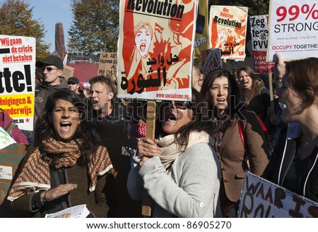 THE HAGUE - OCTOBER 15:  An unidentified women holding banners of Socialist party shouting during the Occupy protest on October 15, 2011 in The Hague, The Netherlands. - stock photo