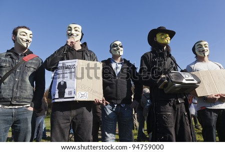 THE HAGUE – OCTOBER 15: Five masked members of Anonymous protesting during the Occupy protest on October 15, 2011 in The Hague, The Netherlands. - stock photo
