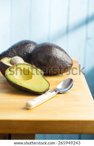 the halved avocado on kitchen table - stock photo