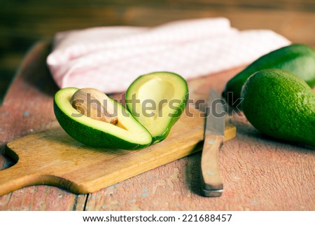 the halved avocados on old wooden table - stock photo