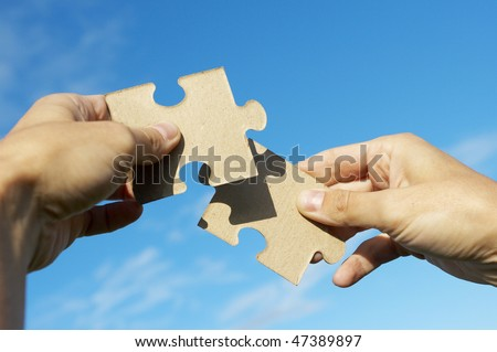 The hand holds puzzle on a background of the sky - stock photo