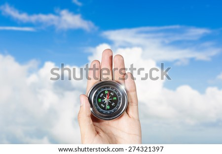 The hand of a man holding a magnetic compass over a blue sky - stock photo