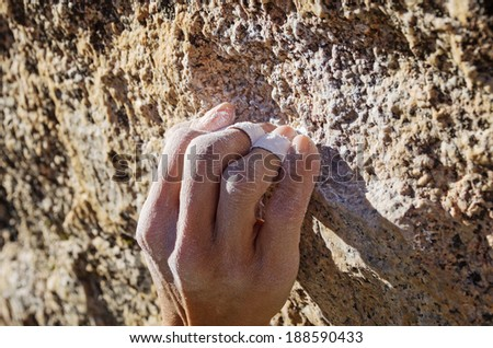 the hand of a woman climber in a crimp grip grabbing a small granite rock climbing hold - stock photo