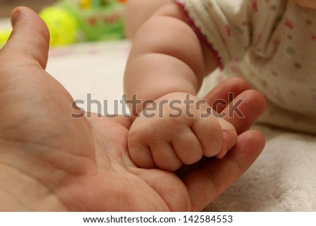 The hand of the child holds a hand of the adult - stock photo