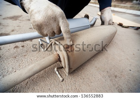 The hand of the man showing on a rust of the muffler, nearby the new muffler - stock photo