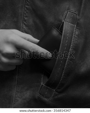 The hand of the white man pulls out a wallet from another's pocket. The concept of stealing money, crime. Black and white photo - stock photo