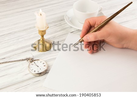 The hand of the woman writes with the ancient handle on paper - stock photo