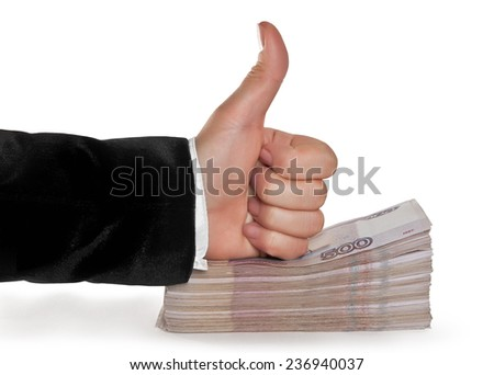 The hand on the stack of Russian banknotes with a raised thumb - stock photo