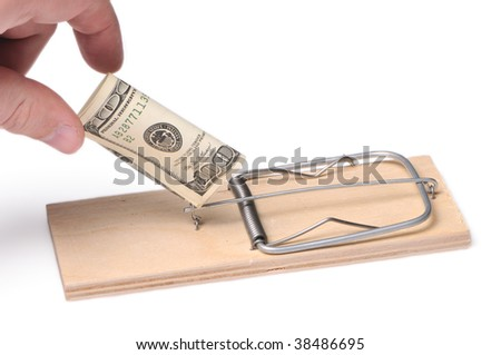 The hand which is taking out dollars from a mousetrap - stock photo