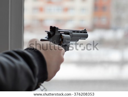 The hand with the gun at the window - stock photo
