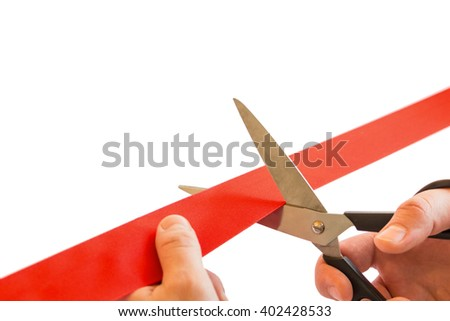 The hand with the scissors cut a red ribbon. - stock photo