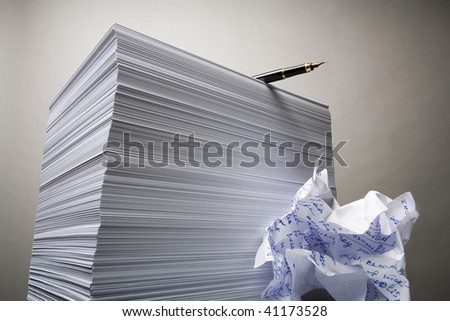 The handle lying on a pile of blank leaves of a paper, near to a crushed sheet of paper - stock photo