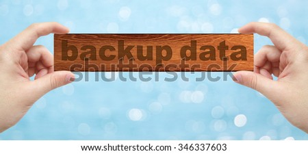 The Hands holding a wood engrave with word backup data with bokeh background - stock photo