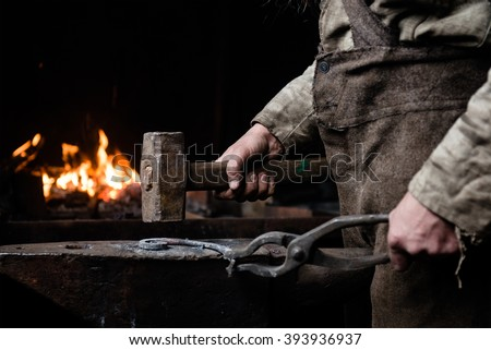 The hands of a blacksmith at work in the smithy - stock photo