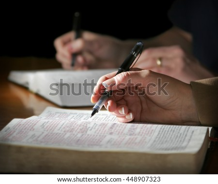 The hands of a couple are highlighted as they study the Holy Bible together - focus point on the woman's foreground hand. - stock photo