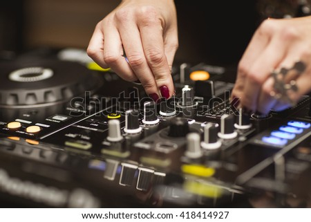 The hands of a female dj using a mixer - stock photo
