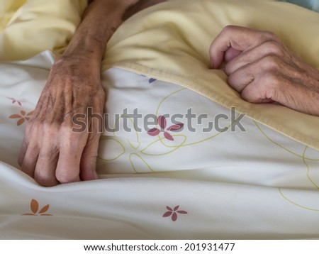 The hands of a very old and skinny woman in bed - stock photo
