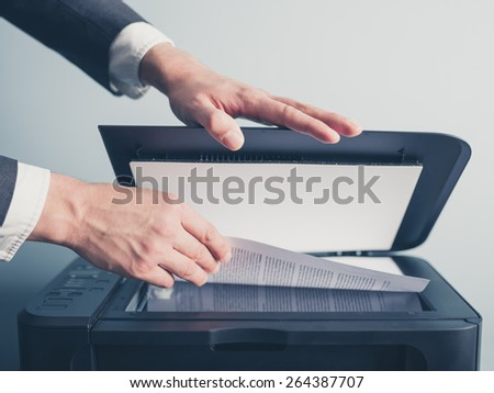 The hands of a young businessman is placing a document on a flatbed scanner in preparation for copying it - stock photo