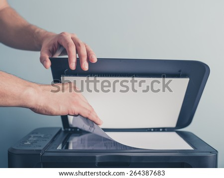 The hands of a young man is placing a piece of paper on a flatbed scanner in preparation for copying it - stock photo