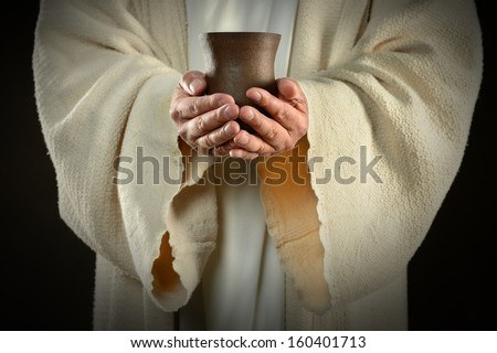 The hands of Jesus holding wine cup, symbol of communion - stock photo