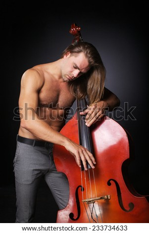 The handsome man with long hair and naked torso is hold double-bass - stock photo