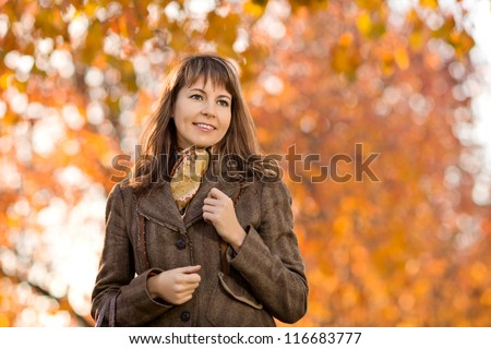 The happiness mature beautiful woman, horizontal portrait,  outdoor in park, autumnal day - stock photo
