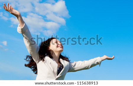 The happy attractive woman with the lifted hands. Against the blue sky - stock photo