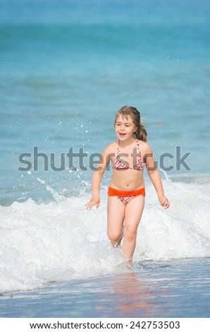 The happy child runs on the seashore - stock photo