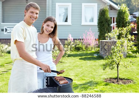 The happy couple makes barbecue - stock photo