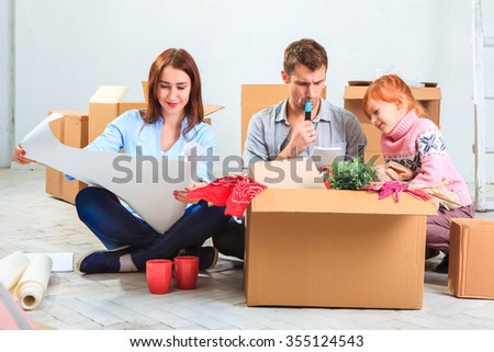 The happy family  at repair and relocation. The family planing  to accommodation on a background of boxes - stock photo