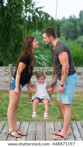 The happy family has a rest outdoors. The baby daughter rides a swing. - stock photo