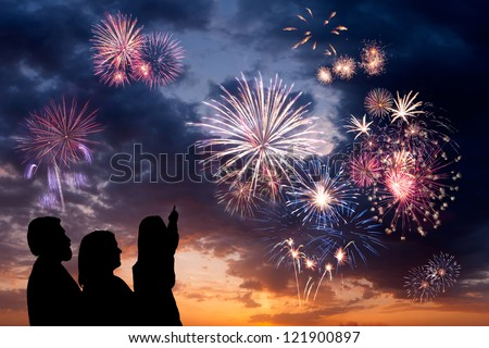 The happy family looks beautiful colorful holiday fireworks in the evening sky with majestic clouds,  long exposure - stock photo