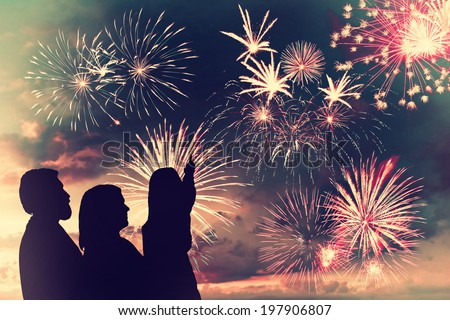 The happy family looks holiday fireworks in the evening sky - stock photo
