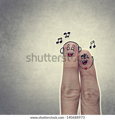 the happy finger couple in love with painted smiley and sing a song - stock photo